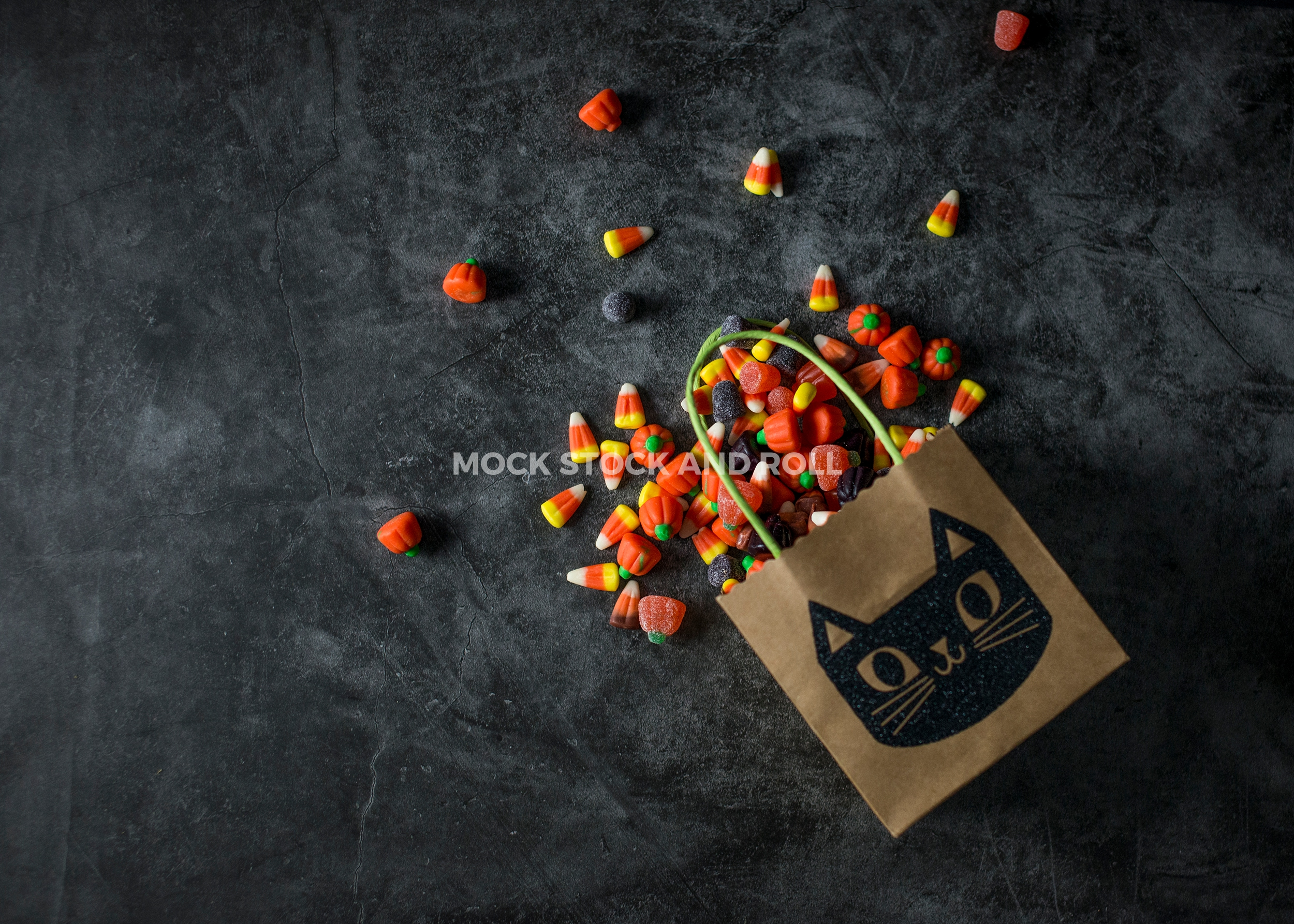 Dark and moody Halloween styled stock photos with candy corn from Mock Stock and Roll Photography.