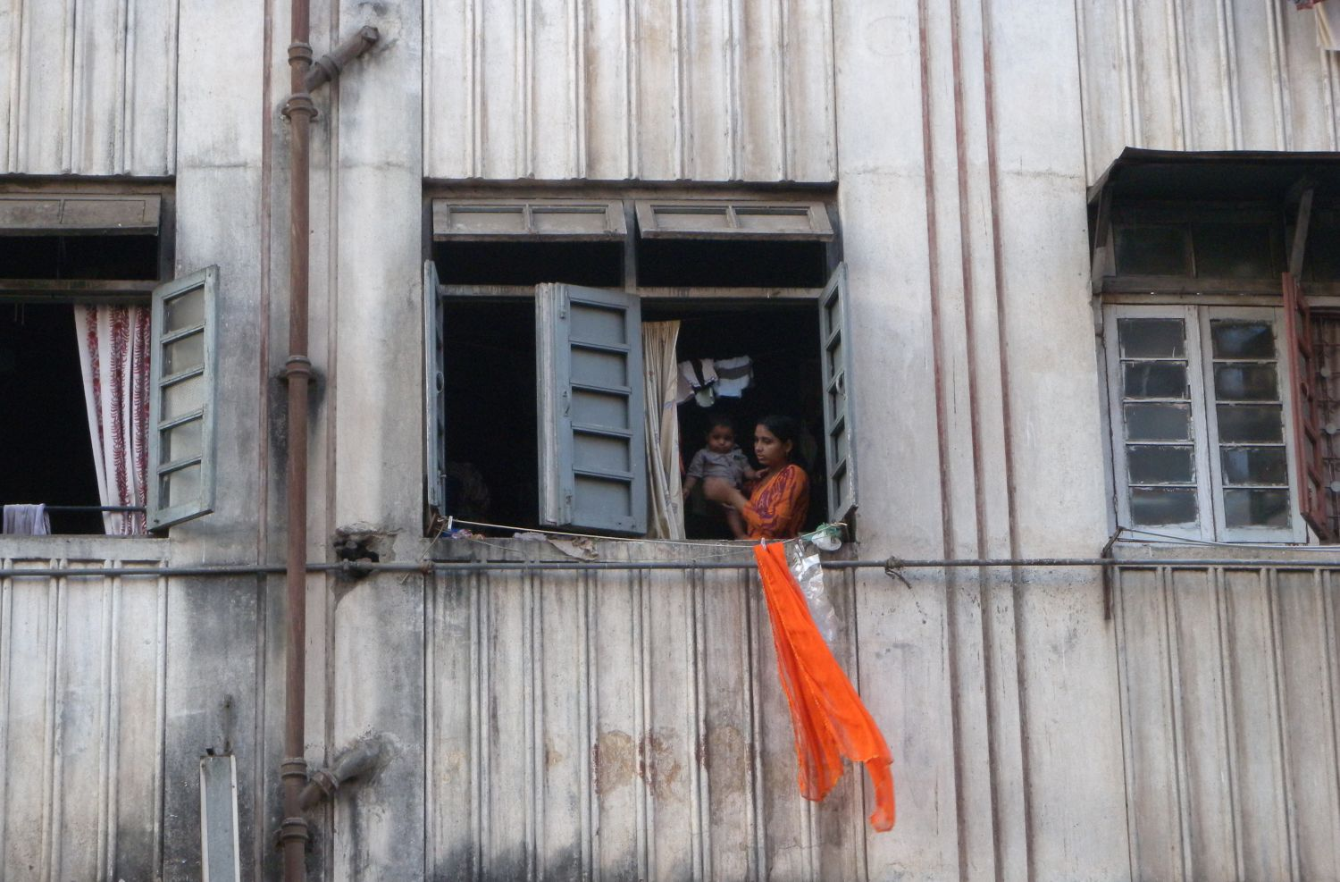 Mumbai - Bombay | Woman with baby looking out the window | Indian building in Mumbai |©sandrine cohen