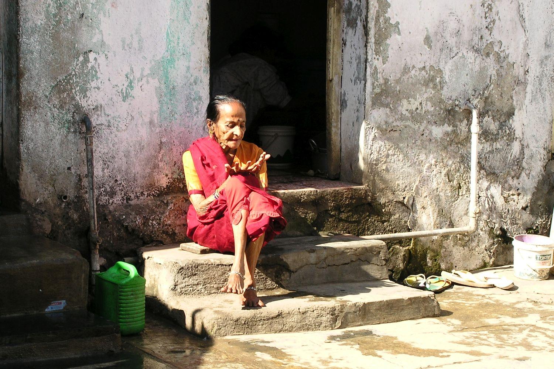 Mumbai - Bombay | Indian woman on the slum | Slum in Mumbai | Woman with red dress in slum season | ©sandrine cohen