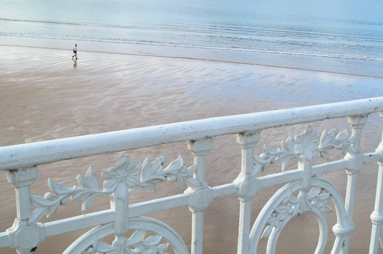 San Sebastian | Donostia | Spain | A man on the beach | Concha | White barrier, emblem of san sebastian | photo sandrine cohen