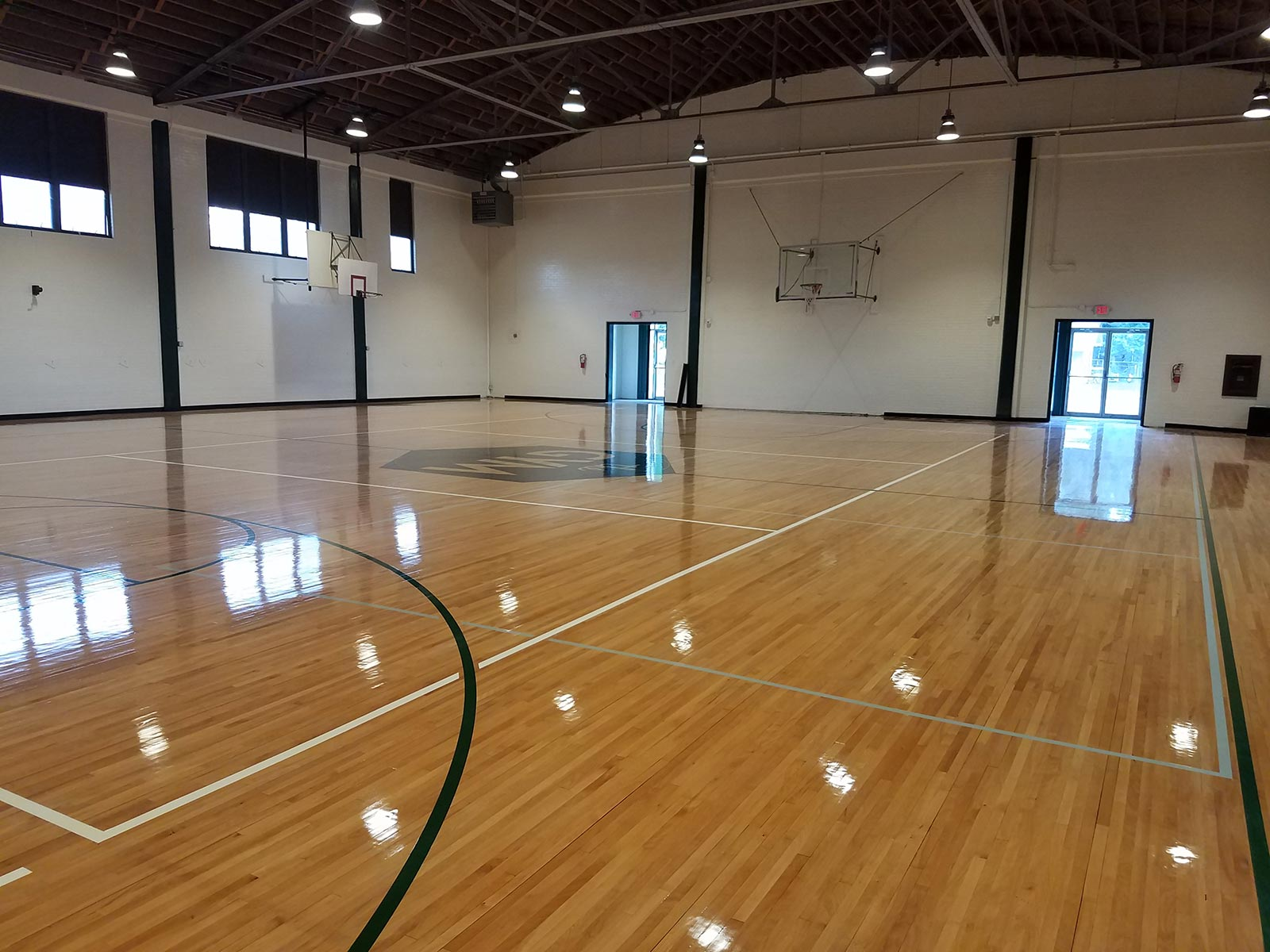 The restored original floor of the gymnasium at the historic high school campus in Taylor.  The 1930s gymnasium now serves as an event center with new restroom, bar and kitchen facilities. The campus required a Planned Development for reduced parking minimums, additional permitted uses and amplified sound, and the gymnasium required a building permit for the new restrooms, demo of interior walls, life safety features and commercial kitchen. We wrote the Planned Development documents, negotiated with city staff and presented the Planned Development to Taylor City Council for approval, which was unanimous.