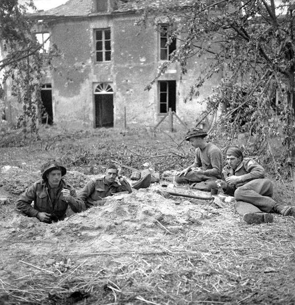 Soldiers of the Highland Light Infantry of Canada having breakfast in Buron, France on 9 July 1944, the day after they took the village (Lieut. Michael M. Dean / Canada. Dept. of National Defence / Library and Archives Canada / PA-131399).