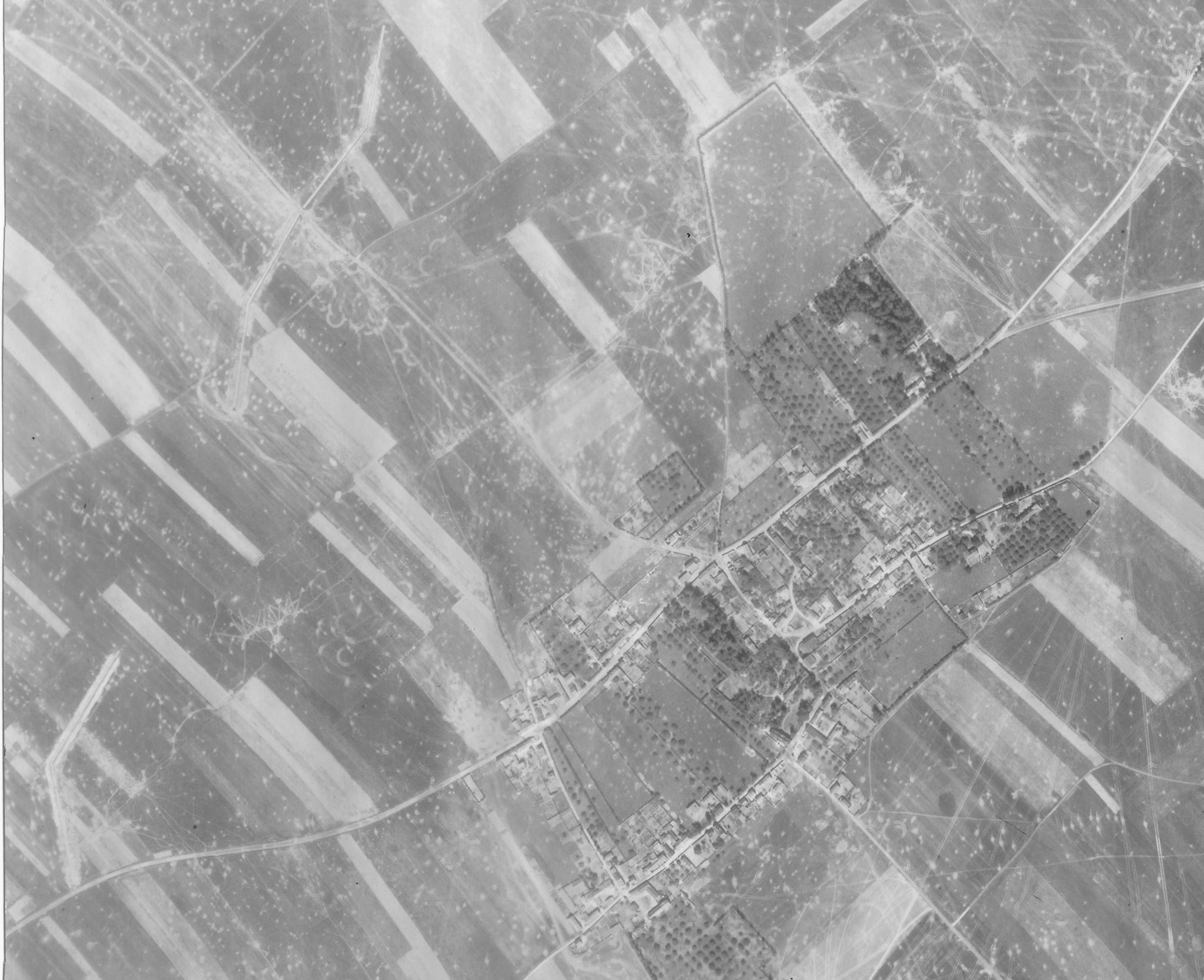 An aerial reconnaissance photo of Buron, taken on 24 June 1944, clearly showing the anti-tank ditches the Germans built for the village's defence. Tank tracks and cratering indicate the heavy fighting in the area (LCMSDS Air Photo Collection 307/4087).