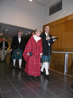 The piping in of the haggis - Senator Joyce Fairbairn, haggis bearer Gordon Campbell, and Ian McKenna (MC)