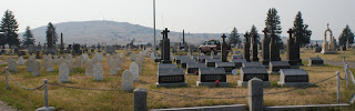 As you can see, this section in split in half. The people on the left have white table headstones. The persons on the right have large black granite headstones. Why the division? Nuns are buried on the left; priests on the right.