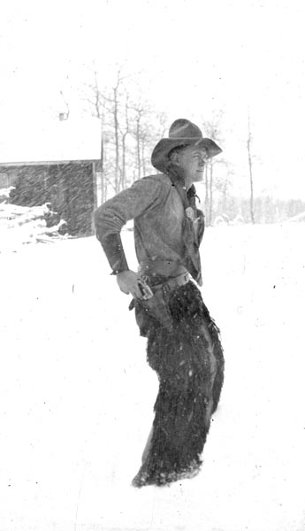 """Photograph of Stephen Harwood posing for a  self   portrait  photograph as a quick draw cowboy.  Arthur """"Pop"""" Harwood came to Waterton Lakes National Park circa 1914 where he was employed in a variety of jobs before becoming the postmaster, a position he held until the 1950s. He had one son, Stephen, who was an avid photographer and outdoorsman who became a mechanic with the park, married and raised one son, Marvin.  Courtesy the Galt Museum & Archives, accession number:  20151083108"""