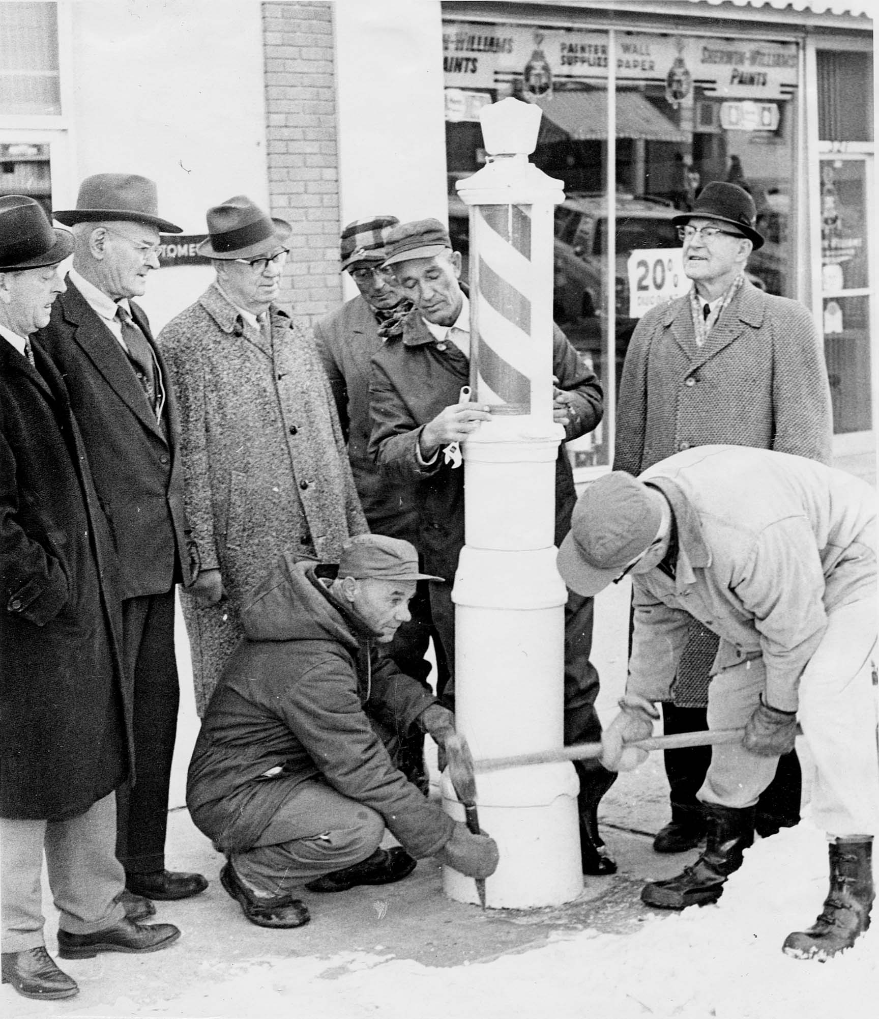 """Caption from the Lethbridge Herald November 29, 1965:  """"SAVING BARBER POLE FOR POSTERITY ~ When the late James and Harold Westbrook put this barber pole in place on 6th St. S. some 40 years ago they probably never dreamed it would end up in the Lethbridge and District Museum. But sidewalk barber poles are relics of the past and this one from the Westbrook Barber Shop is believed to be one of the last in the nation. Left to right are R.E. (Bob) Faulds, present owner of the shop; Andrew Staysko and Chris Gibson, museum officials; city employees Nick Poneck (immediately behind the pole); John Lanning (kneeling with chisel) and Charles Kunz (with hammer); and George McKillop, also of the museum.""""   Photo courtesy the Galt Museum & Archives: 19730307000"""
