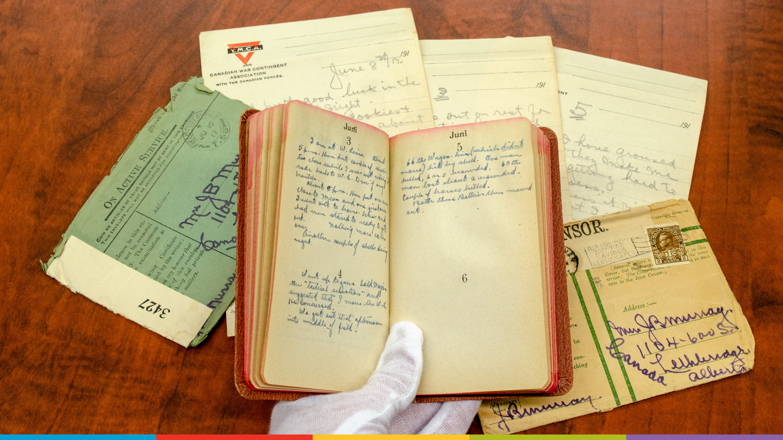 A photo of a gloved hand holding a journal from the Galt's Archives with other archival documents behind.