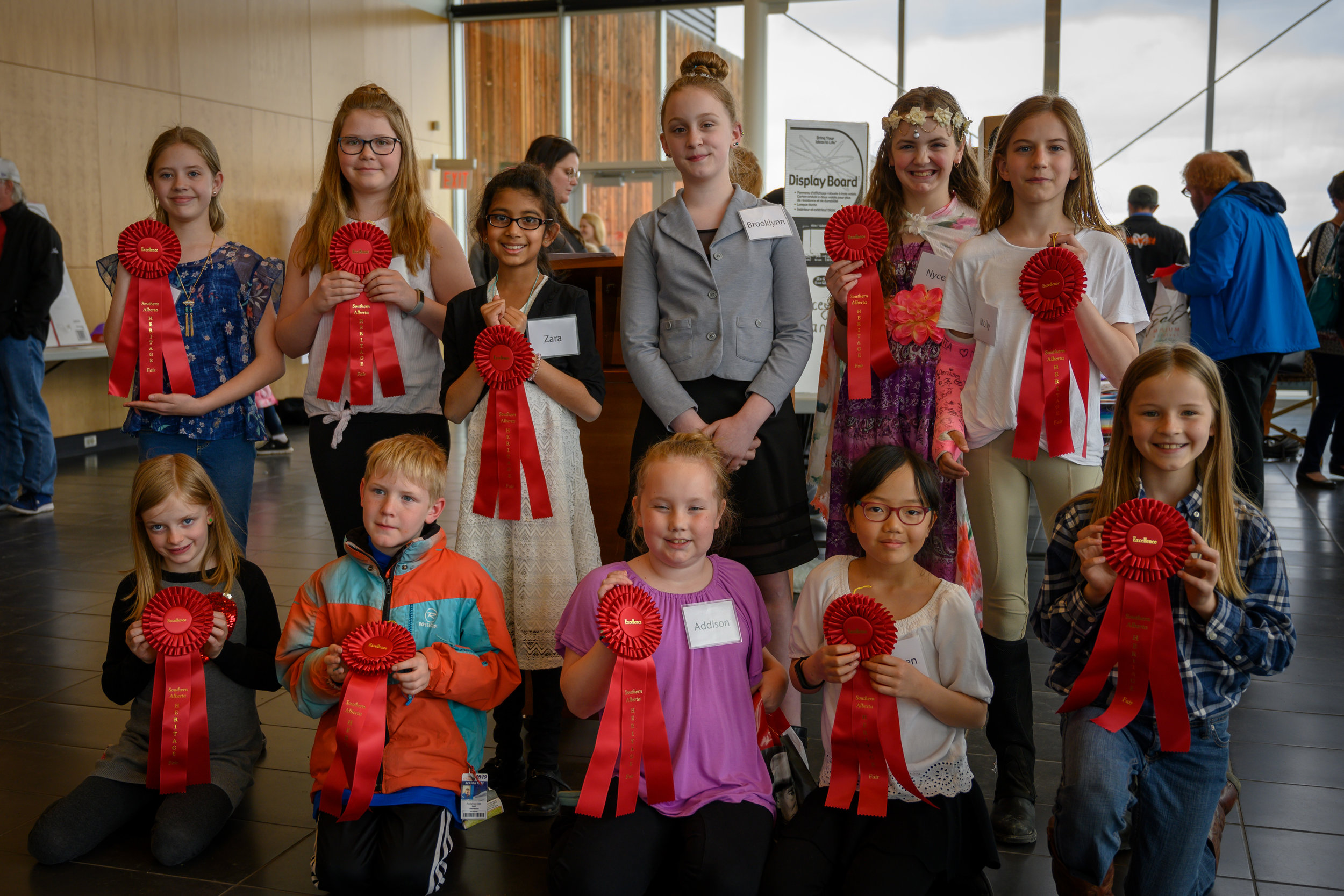 A photo featuring many of the students who won awards of excellence in history for their Heritage Fair projects  Standing:  Courtenay Shampaign  and  Preslee Losey  — Great Canadian Women: Inspiring Today's Girls,  Zara Enayetullah  — Craig Kielburger,  Brooklynn Allen  — the Great Depression,  Nycea Hazelwood  — Truth & Reconciliation,  Molly Buteau  and  Hanna Friesen  (kneeling) — Horses in the Day.  Kneeling:  Aislin Falkenberg  — the High Level Bridge,  Samuel Campmans  — Post WWII Dutch Immigration,  Addison Carey  — Head‑Smashed-In Buffalo Jump,  Kathleen Wu  — Chinese Immigrants to Canada.