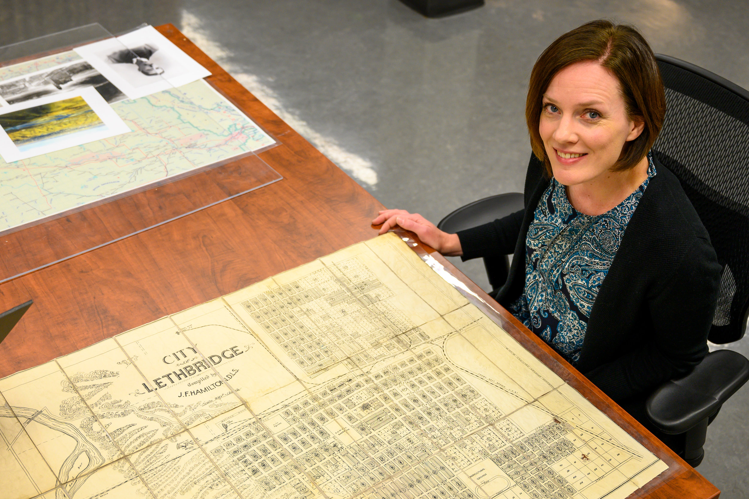 Curator Aimee Benoit with a 1909 map of Lethbridge.