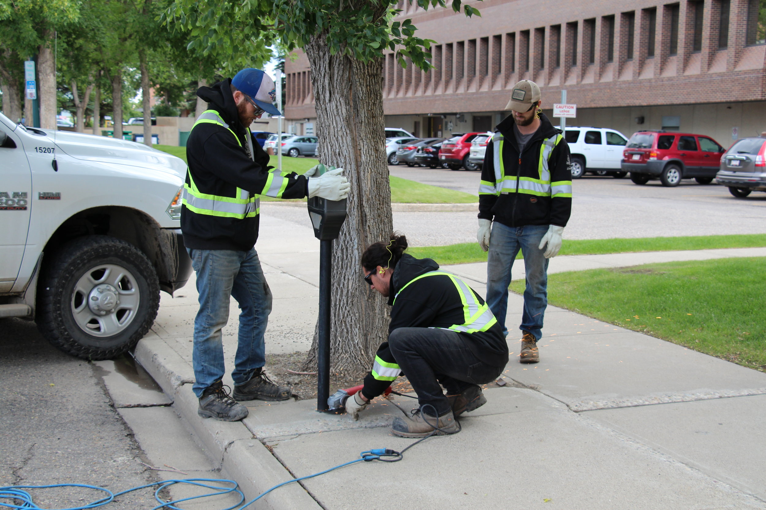 Workers removing a parking metre from the 300 block of 3 Street South, which was later donated to the Galt Museum & Archives.