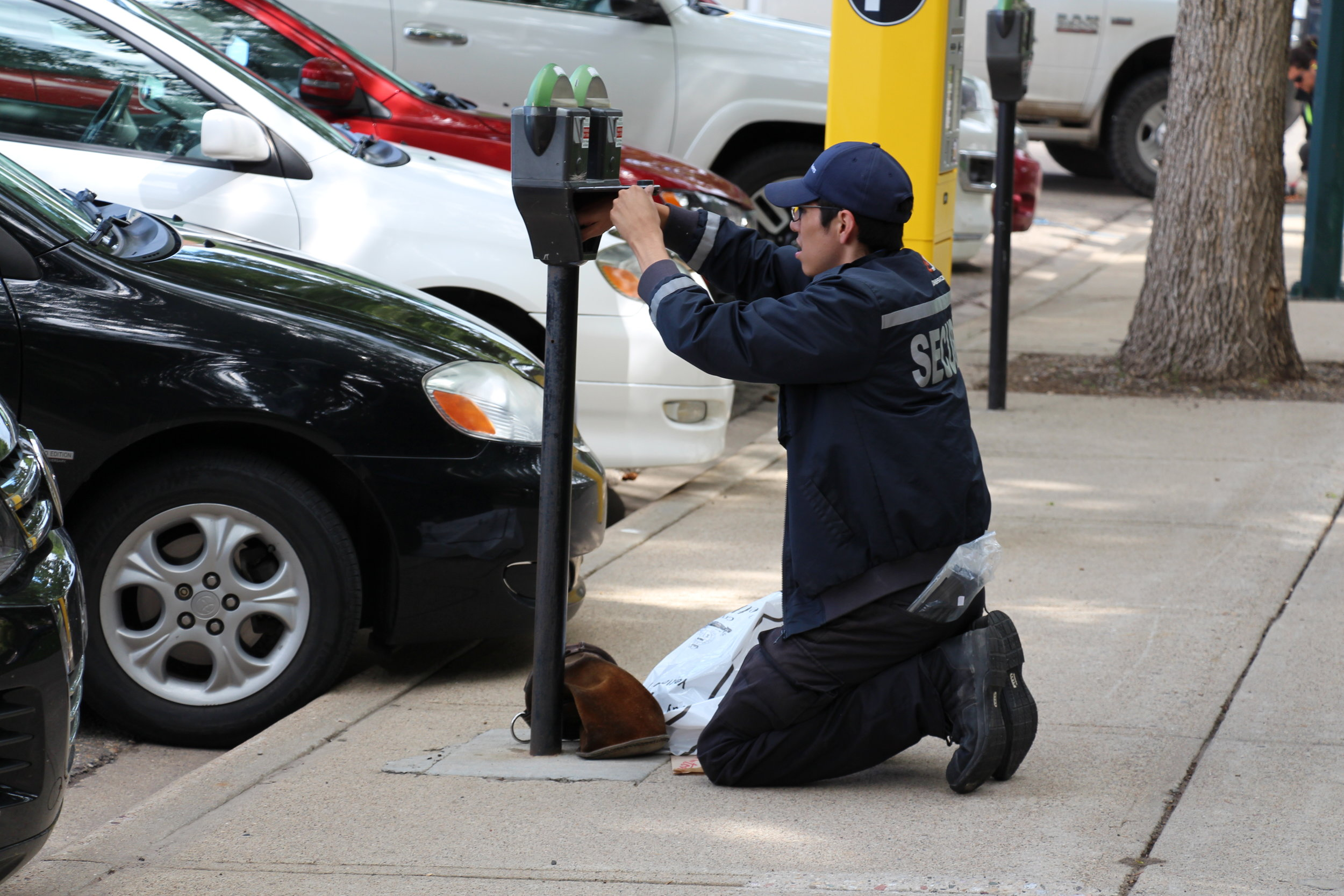 A person  works on a parking meter, with a new yellow parking kiosk in the background.