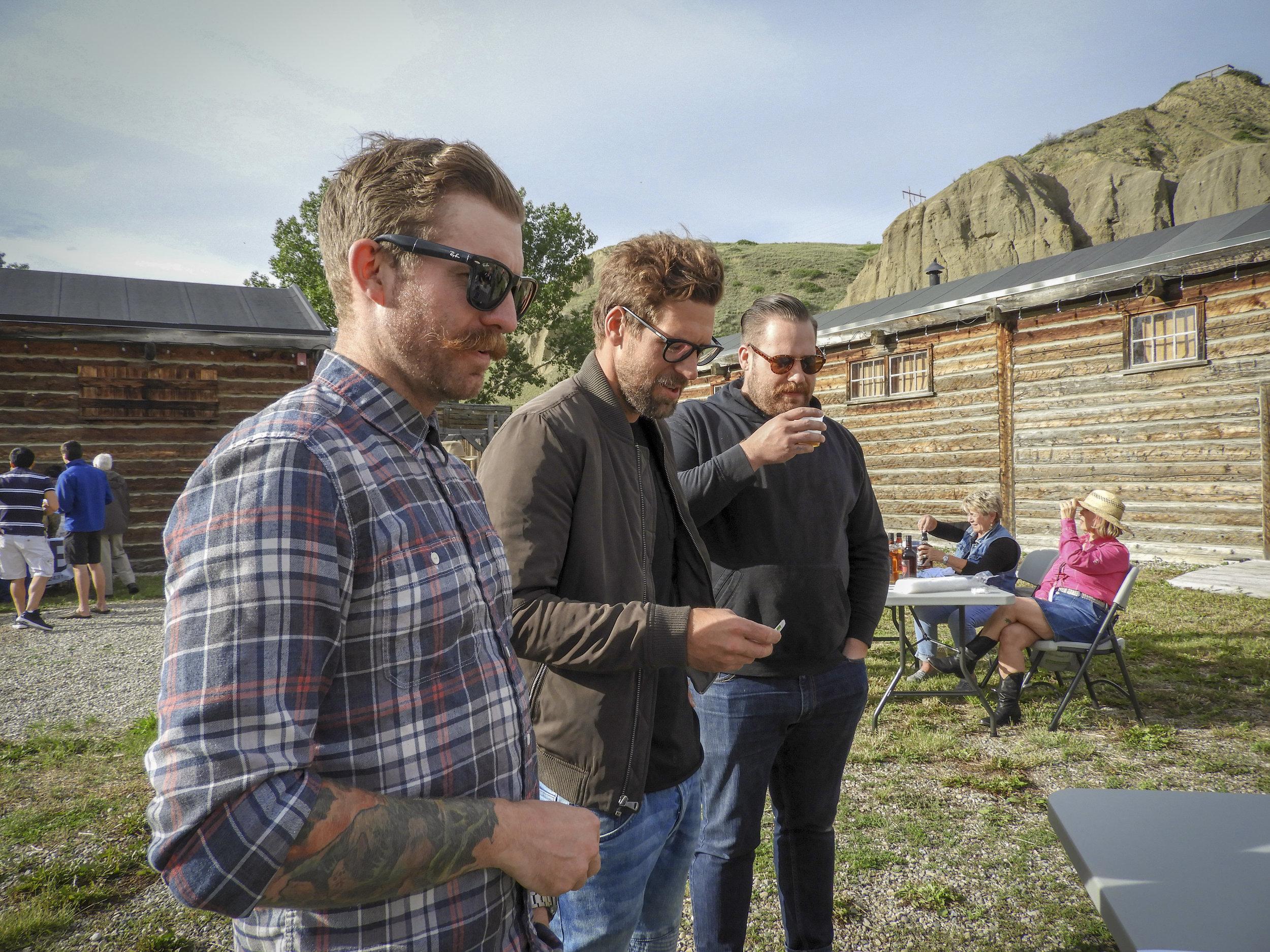 Three individuals sampling drinks at Trader Day.