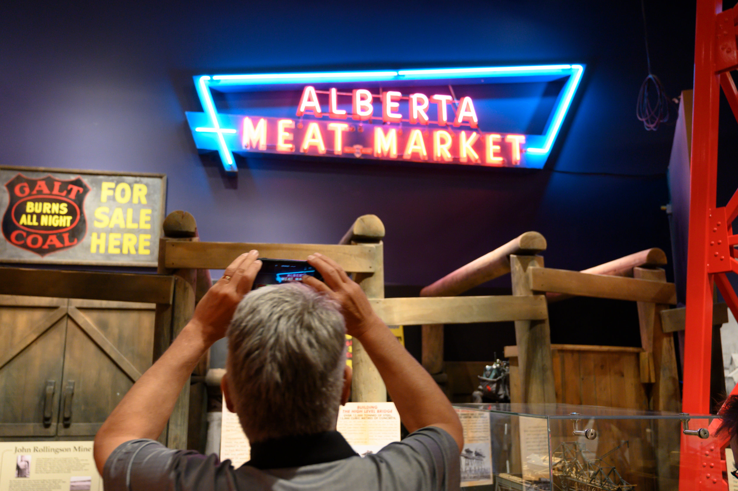 CTV Reporter Terry Vogt taking a video of the inaugural lighting of the Alberta Meat Market sign in its permanent home in the Discovery Hall of the Galt Museum & Archives.