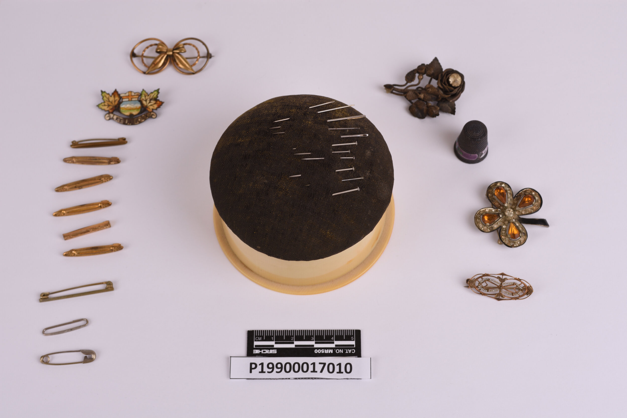 A pin cushion and pins and clasps donated to the Galt by Laurie Davis.   Photo courtesy the Galt Museum & Archives: 19900017010