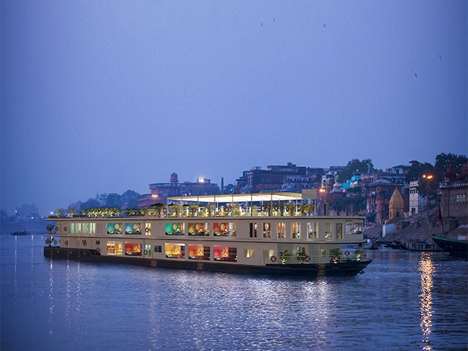 Ganga Vilas - To be launched in 2020, Ganga Vilas will be the new luxury river cruise vessel with 18 suites and superlative facilities. It blends heritage and modern amenities with minimalist designs, and redefines the boutique experience on water. Its 40-seat restaurant, located on the Main Deck, serves Continental and Indian delicacies. The al fresco ambience of the Upper Deck features a bar where you can simply lounge with your friends or enjoy your favourite drink. There is also an area with comfortable deck chairs to sunbathe and a well-appointed spa with professional therapists.