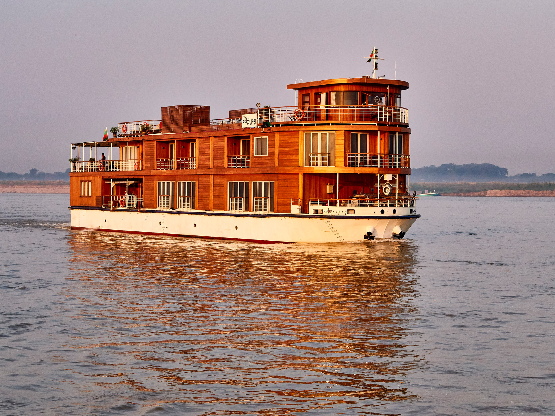 RV Paukan 2012 - This small cruising boutique hotel was built on the banks of the Yangon River, a place with a 200 years-old tradition of excellent craftsmanship. It is a gem of a vessel – a compact but elegant ship made of teak with a hull of marine steel. The walls and floors are of timber with each plank carefully chosen to display the beautiful grain. The décor is modern chic, with a few traditional motifs, wooden figures, fabrics and paintings to give a touch of Myanmar culture. The ship takes 34 passengers in its 18 staterooms, twin and double. All the staterooms are tastefully decorated and comfortable with a private bathroom.