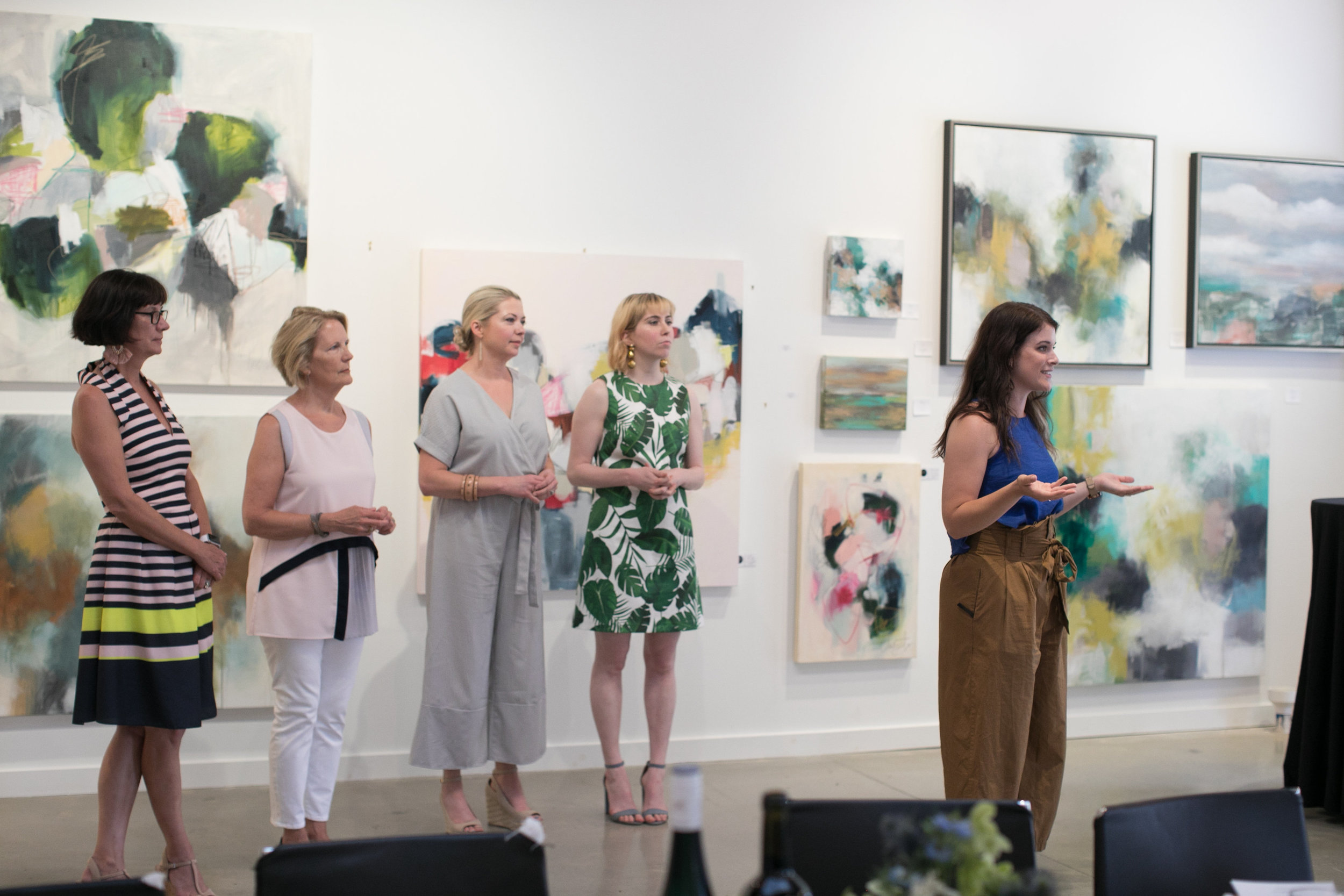 Art Farm Director Megan Schaeffer introduces artists Lulie Wallace and Raven Roxanne to Art Over Dinner guests at Grange Hall.