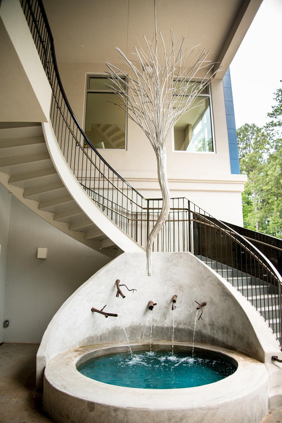 Robert Rausch designed the light fixture that hangs above a fountain alongside the staircase fabricated by Gault Designs. Photo by Mia Yakel.