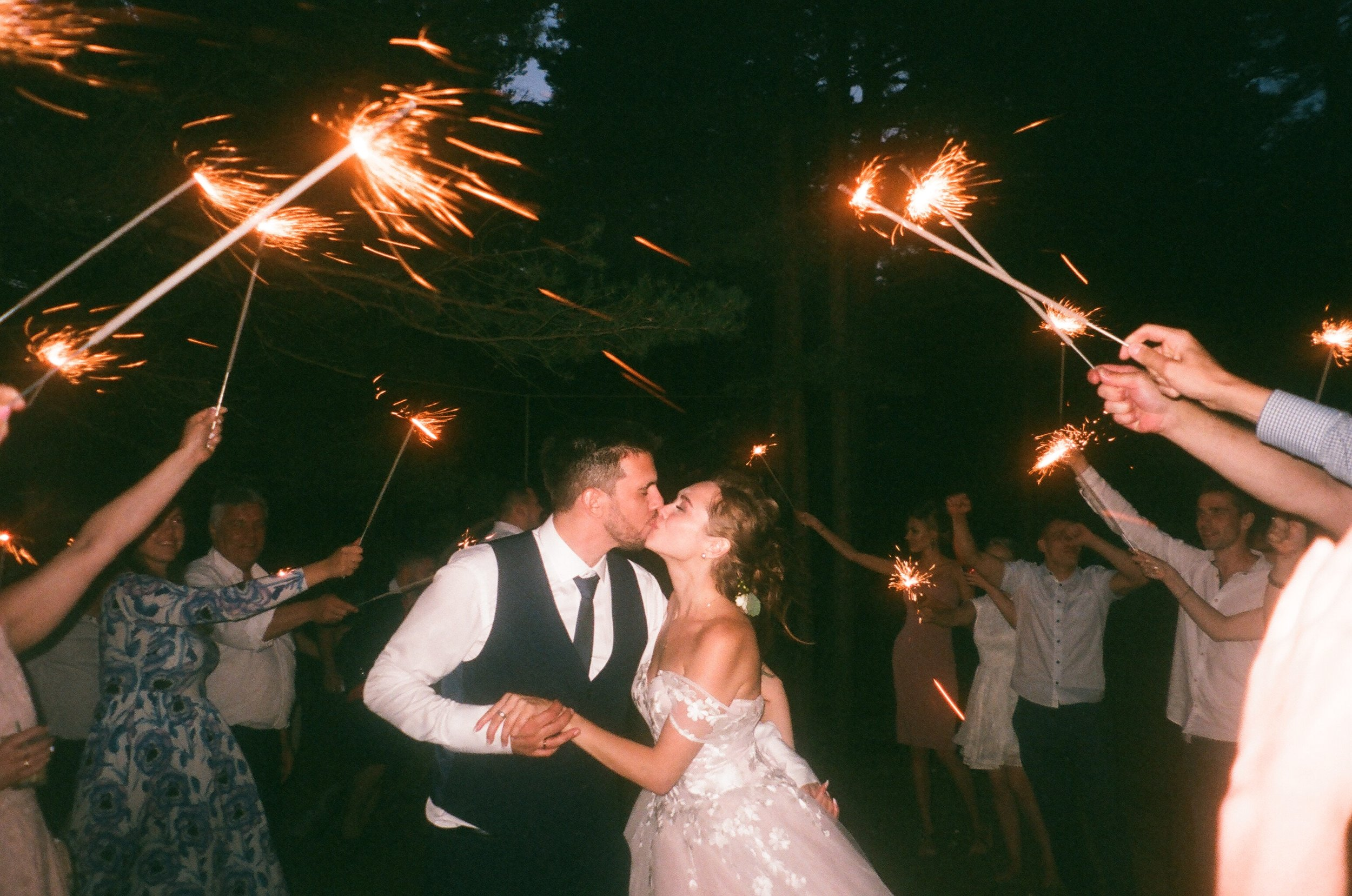 Just married couple kissing beneath sparklers held by party guests