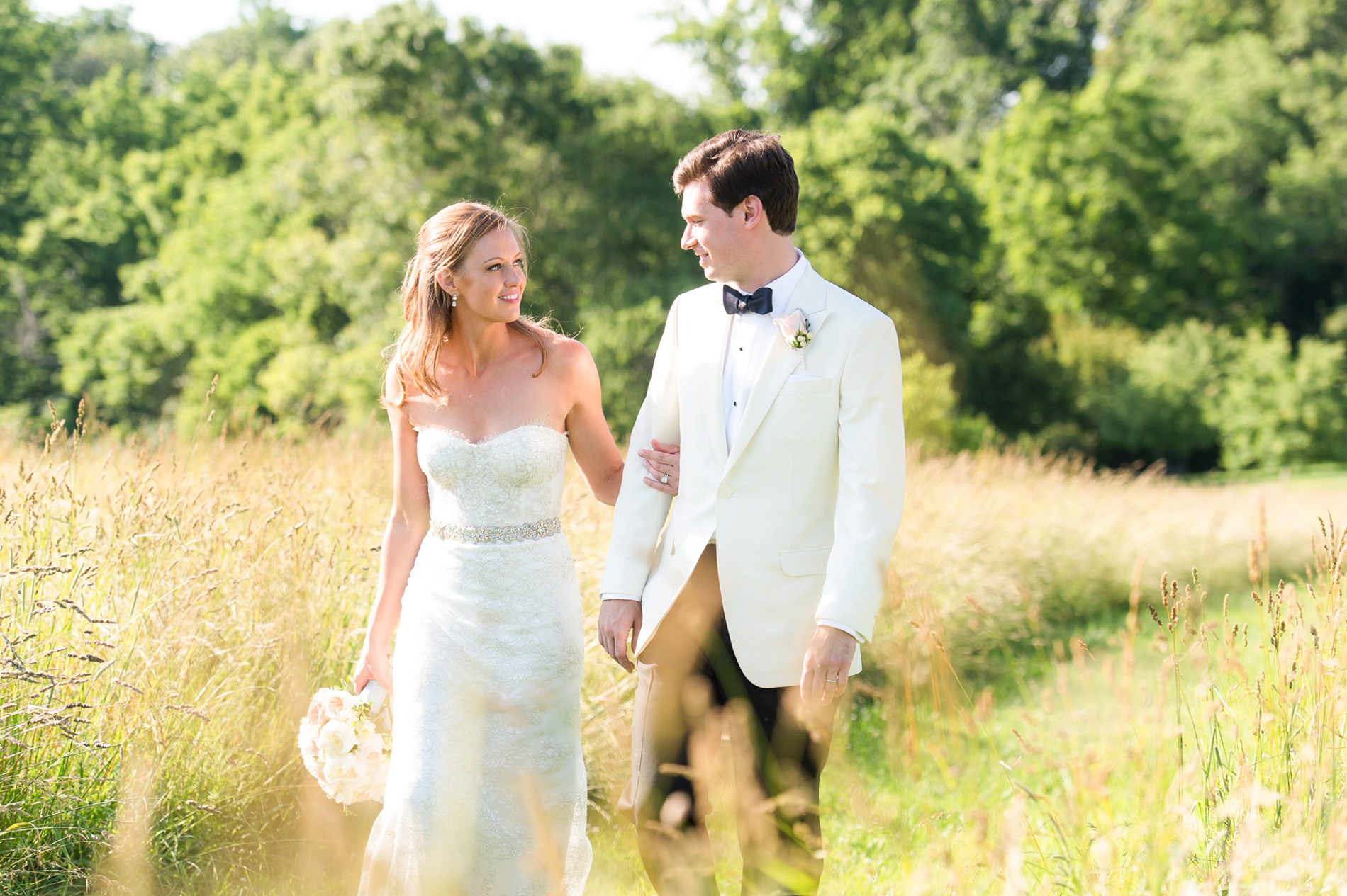 bride and groom walking hand-in-hand outdoors