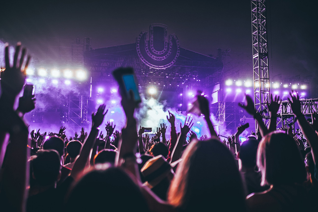 Excited concert crowd with raised hands