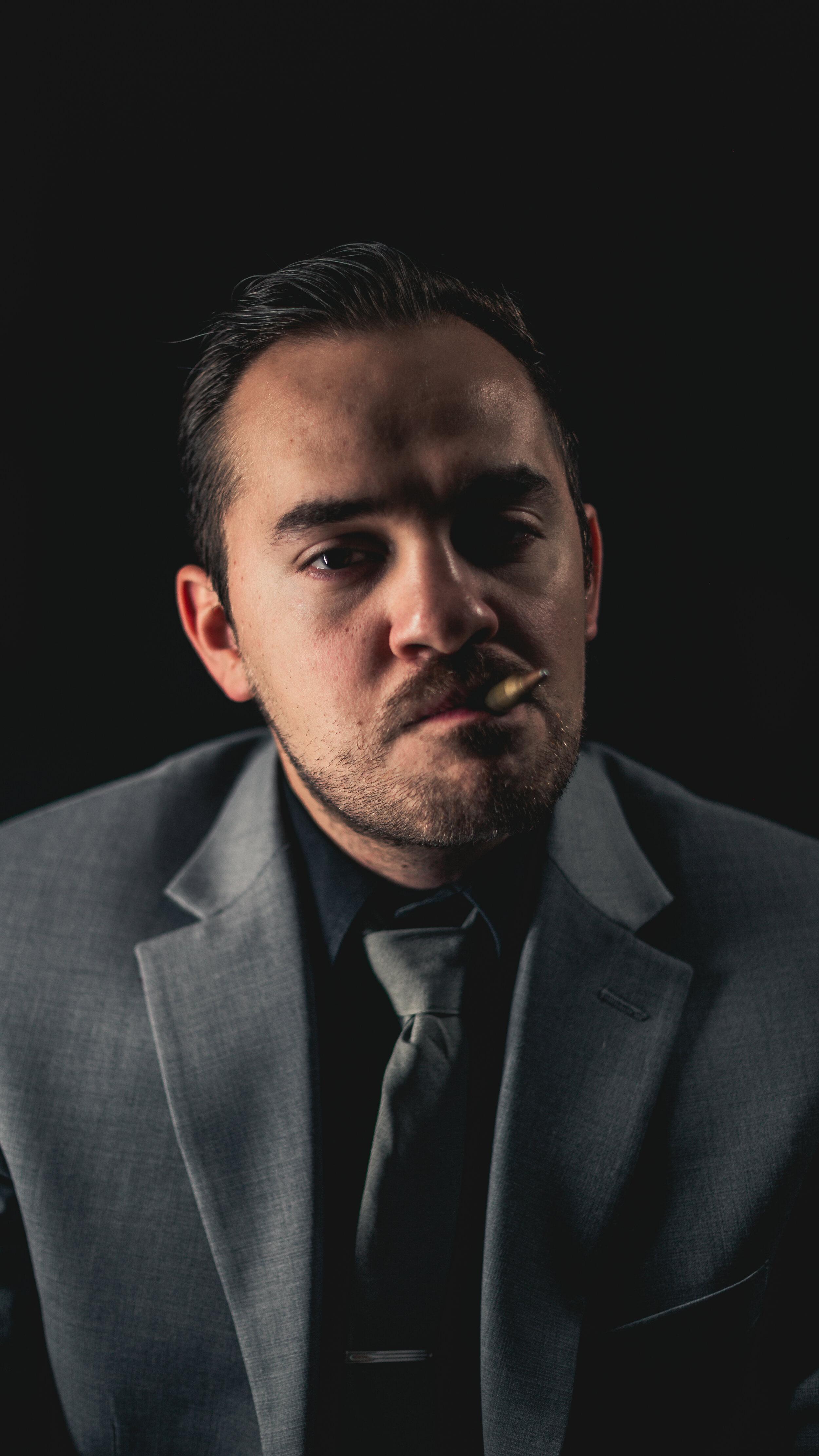 portrait-man-bullet-in-mouth-dressed-formal.jpg