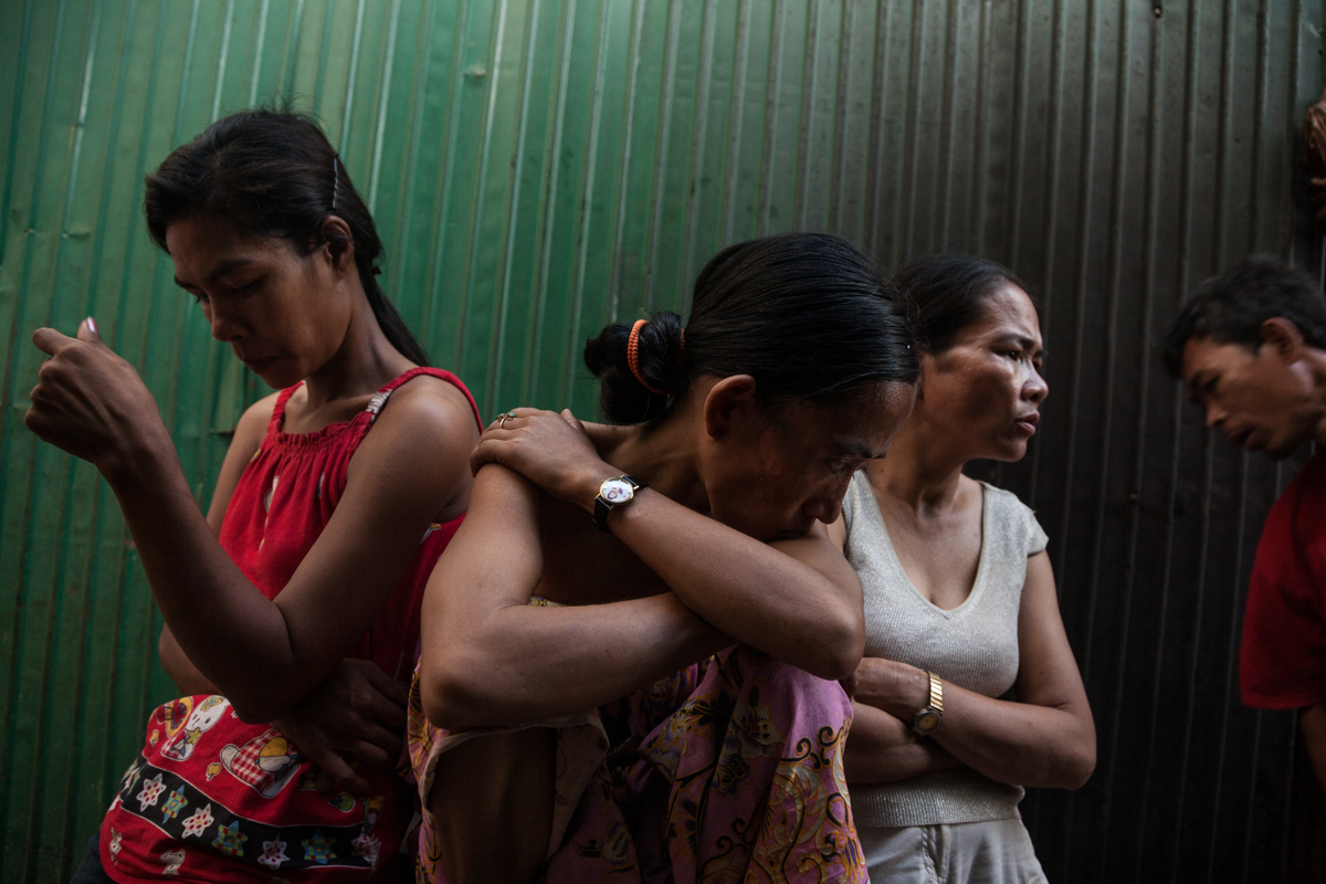 March 03, 2009 - Phnom Penh, Cambodia. As Phnom Penh sees a rapid rise in development and investment, evictions are common in Cambodia's capital as developers are reclaiming land from poor communities. Vin Thy (C) and Chanty (R) in Borei Keila, their community is slated for a second eviction. The first one saw them move out of their homes in Borei Keila and relocated to nearby corrugated iron sheds; their pending eviction will send them to live on the outskirts of the capital. © Nicolas Axelrod / Ruom