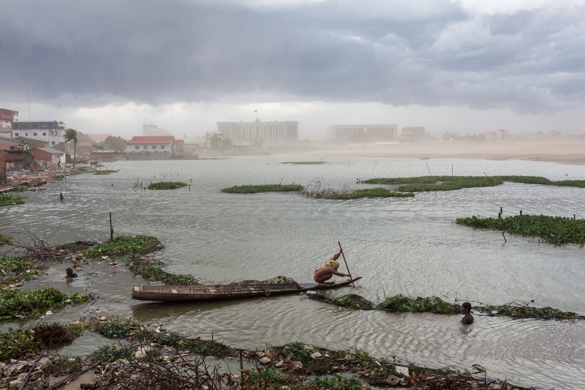 July 07, 2011 - Phnom Penh, Cambodia. A woman paddles her boat against an a storm on Boeung Kak lake. The new buildings of the Council of Ministers and the office of the prime minister can be seen in the background. The lake was reclaimed to make way for residential and commercial complexes. © Nicolas Axelrod / Ruom