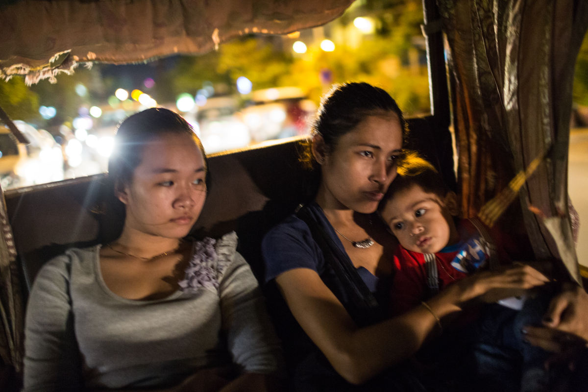 June 05, 2014 - Phnom Penh, Cambodia. Kunthea and her son travel in a tuk-tuk with a family member. Kunthea works as a cleaner for various expat families to support her son. Kunthea went again cultural norms and restrictions to by having a child out of wedlock and raising him as a single mother. © Nicolas Axelrod / Ruom