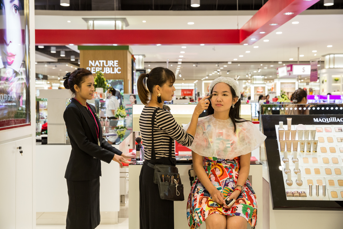 June 28, 2014 - Phnom Penh, Cambodia. A woman gets make-up applied in Cambodia's first mega-mall. © Nicolas Axelrod / Ruom