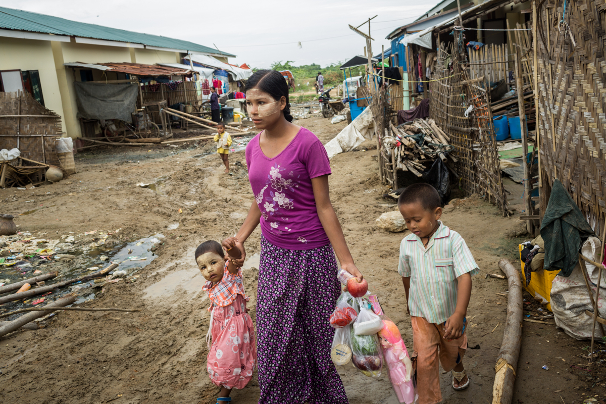 Nov. 02, 2015 - Meikhtila, Myanmar. A mother and her children walk through Chan Aye's area, that was completely destroyed by the religious violence that took place in Meikhtila at the end of March 2013. Government housing have replaced the once barren landscape, yet poor infrastructure and mismanagement have left the community living in strained circumstances. © Nicolas Axelrod / Ruom