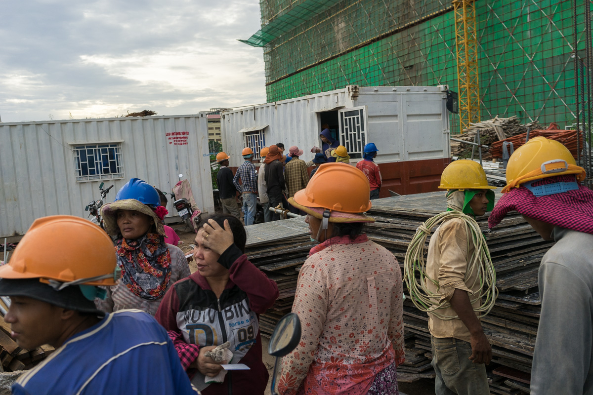 August 11 - 2016 - Phnom Penh, Cambodia. Construction workers wait in line to be paid after a day of work in a construction site in Phnom Penh. Cambodia has undergone rapid economic development in recent decades. However, the country still lacks the infrastructure required for the energy sector to match the pace of development and the capital Phnom Penh consumes 90% of Cambodia's electricity. © Thomas Cristofoletti / Ruom