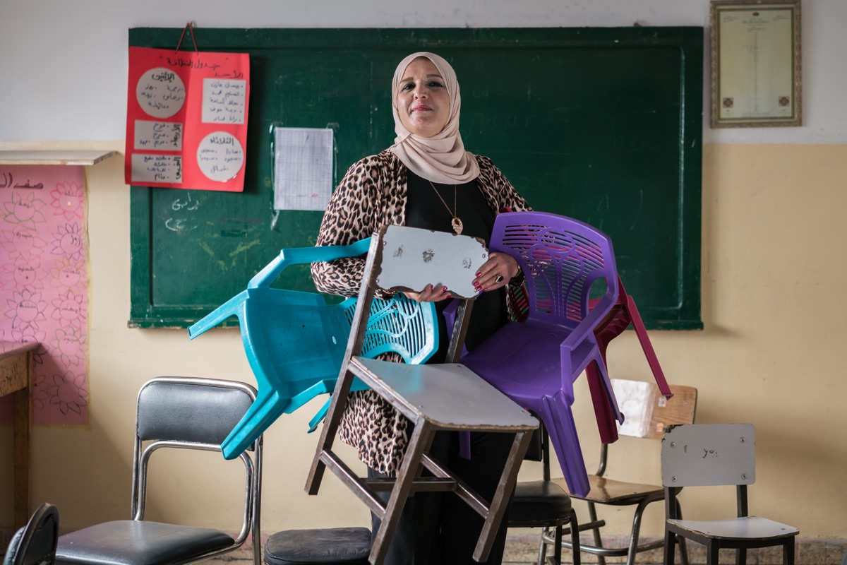 "AMMAN, JORDAN - OCTOBER 1, 2015:  Maha al Ashqar is the principal of Khawla Bint Tha'laba Primary Girls School in a suburb of Amman Jordan. The school, which has 356 students, hosts around 65 Syrian students—many of whom have fled violence and destruction in their country to live as refugees in Jordan. Although her school struggles with overcrowding, Al Ashqar is committed to accepting students. She also recounts this powerful anecdote: A few months after school started this year, a Syrian mother arrived at the front gates asking to enroll her daughter. The women at reception apologized, ""There is no way. This school is full."" The mother was crestfallen. She asked to see the principal and was directed to Al Ashqar. And as she has done so many times before, the principal told the mother that, of course, she would enroll her daughter. But she had one request, ""Please bring a chair."" ""This touched me,"" Al Ashqar explains. ""I saw the tears of many mothers, and it was impossible to tell them that we had no room, to try somewhere else. I told them, just bring a chair with you, even if it's a small plastic chair, and we will make do.""  Syria's civil war has resulted in one of the worst humanitarian crises of our time—one that knows no borders. More than half of Syria's pre-war population has fled their homes due to the violence. A generation of Syrian children has lost access to education and the ability to experience a normal childhood. Of those nearly 12 million people, more than 4 million Syrians have sought refuge in neighboring countries—over 628,000 of them in Jordan."
