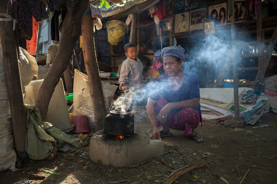 19 December, 2013 - Phnom Penh. A woman boils water on a traditional wooden stove. © Thomas Cristofoletti / Ruom for SNV