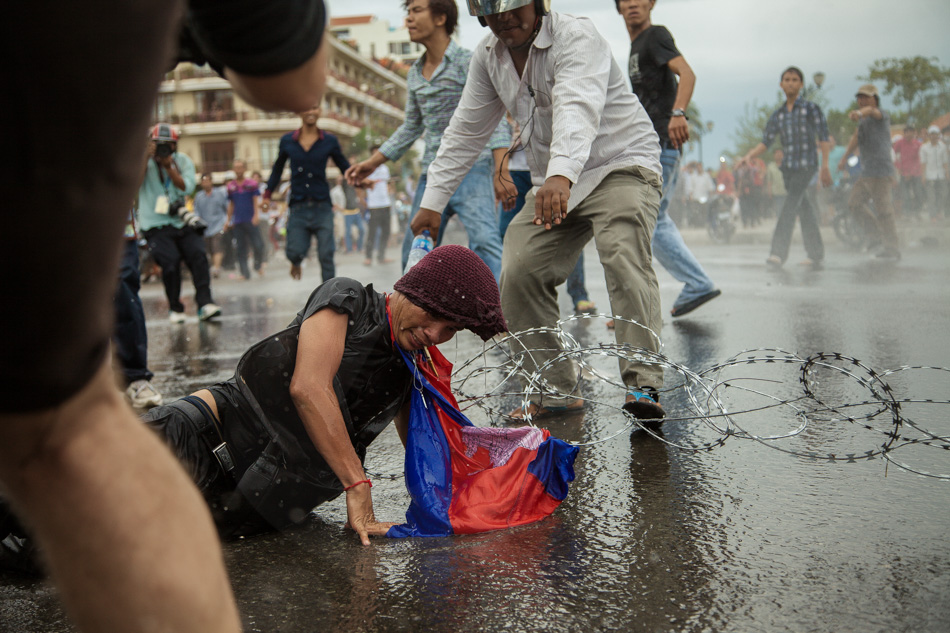 15/09/2013 - Phnom Penh. A CNRP supporter got trapped in the barb wire and injured by a water cannon. © Thomas Cristofoletti / Ruom 2013
