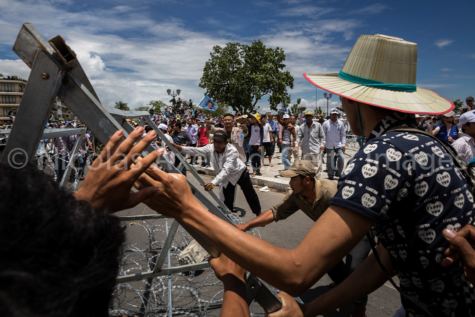 PHNOM PENH, CAMBODIA - SEPTEMBER 15: Supporters of the Cambodia National Rescue Party pull down police barricades as Sam Rainsy, party President, led a march to the Royal Palace on September 15, 2013 in Phnom Penh, Cambodia. The CNRP plan a three day demonstration to contest the Cambodian national election results. (Photo by Nicolas Axelrod/Getty Images)