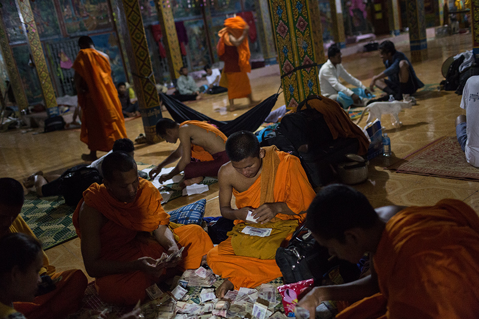 December 04, 2013 - Kampong Thom, Cambodia Monks count the day's alms at the end of day three of the Human Rights Day march into Phnom Penh on National Road 6. © Nicolas Axelrod / Ruom 2013