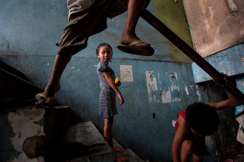 Angelica, 8, plays with her siblings in a stairwell next to her family shack near the Osmena highway. Manila, Philippines. Part of a larger story about escaping the poverty cycle in the Philippines.