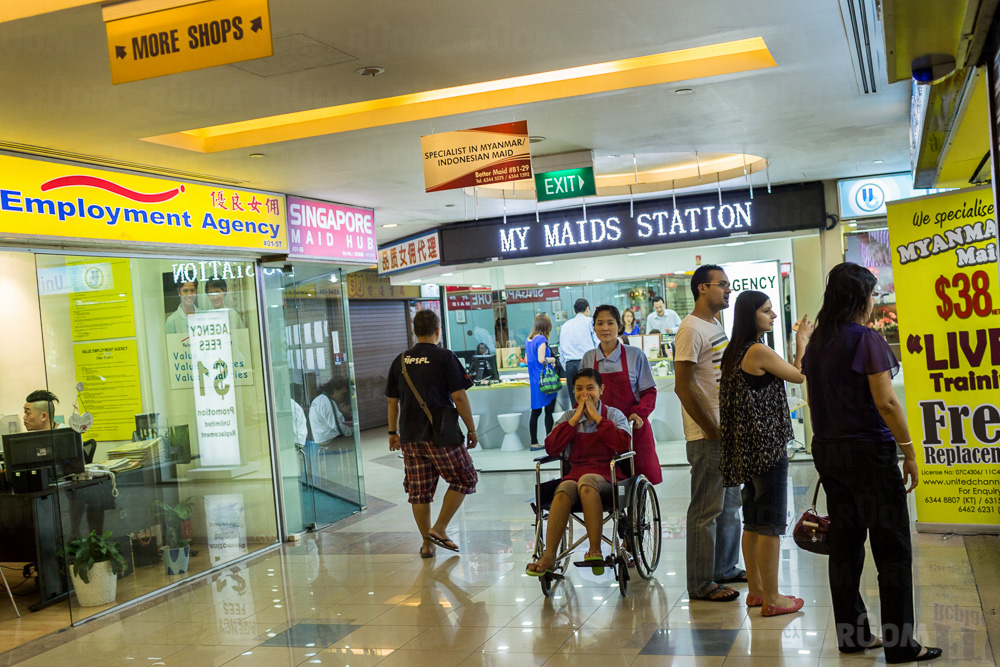 March 24, 2014 - Singapore. Maid agencies at Katong shopping centre. The girl in the wheel-chair is a domestic helper and is being pushed around the hall by another domestic helper in front of a maid agency to promote the work the agency. © Nicolas Axelrod / Ruom