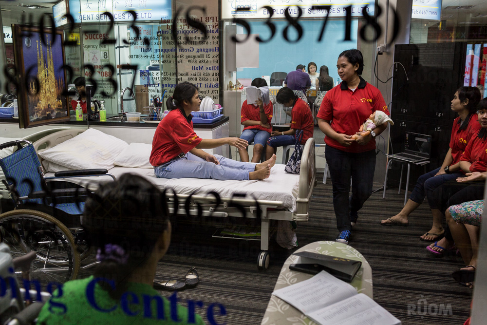 May 10, 2014 - Singapore. Agencies advertising maids for hire, and show their skills in display centre at Bukit Timah shopping plaza. © Nicolas Axelrod / Ruom