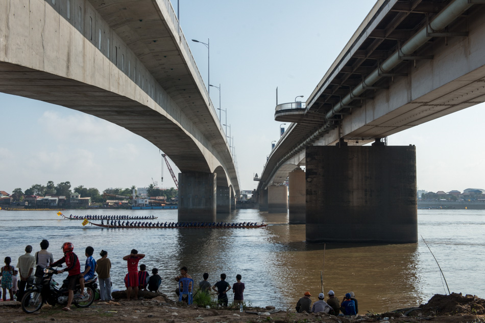 Two boats pass under the Japanese bridge in Phnom Penh during a race. Cambodia's annual 3-day water festival celebrates the reversal of the flow of the Tonle Sap River - an event of large cultural significance because of the river's role in national fishing and agriculture. The event was cancelled for three previous years in a row after the stampede incident in 2010, when nearly 350 people were killed and roughly 750 more were injured.