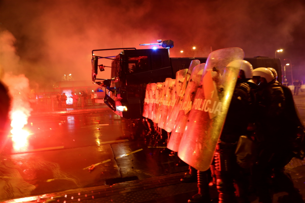 Riot police hides behind shields as stones and flares are hurled in their direction. ©Marta Kasztelan