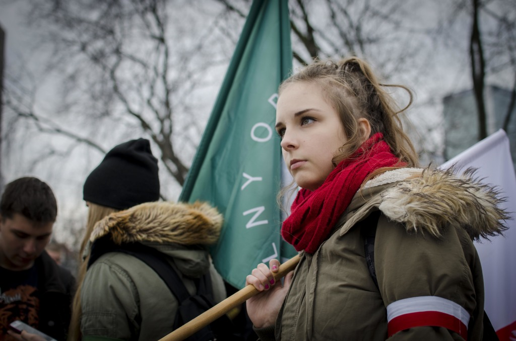 A young woman holds a flag of the National Radical Camp ahead of the rally. ©Marta Soszynska