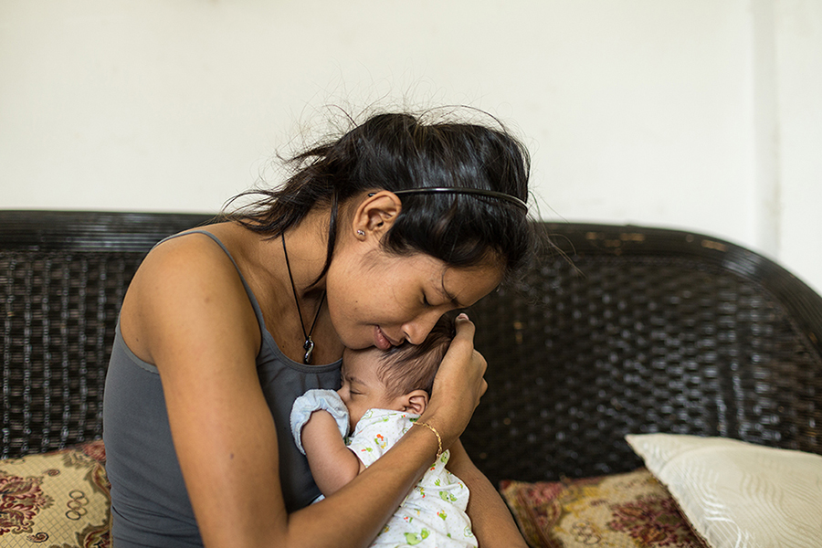 Oct. 27, 2013 - Phnom Penh, Cambodia. Kunthea gives her new born son a hug in her home in Phnom Penh. © Nicolas Axelrod / Ruom