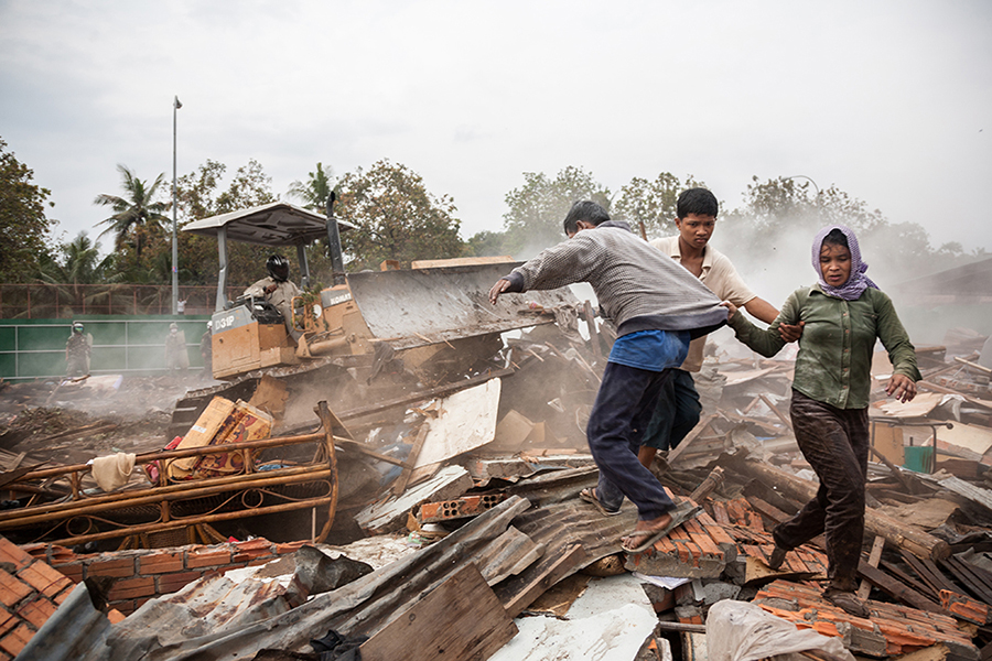 Jan. 24, 2009 - Phnom Penh, Cambodia. Residents flee a bulldozer as it charges over rubble of a destroyed home during the evicition of Dey Krahorm community. © Nicolas Axelrod / Ruom