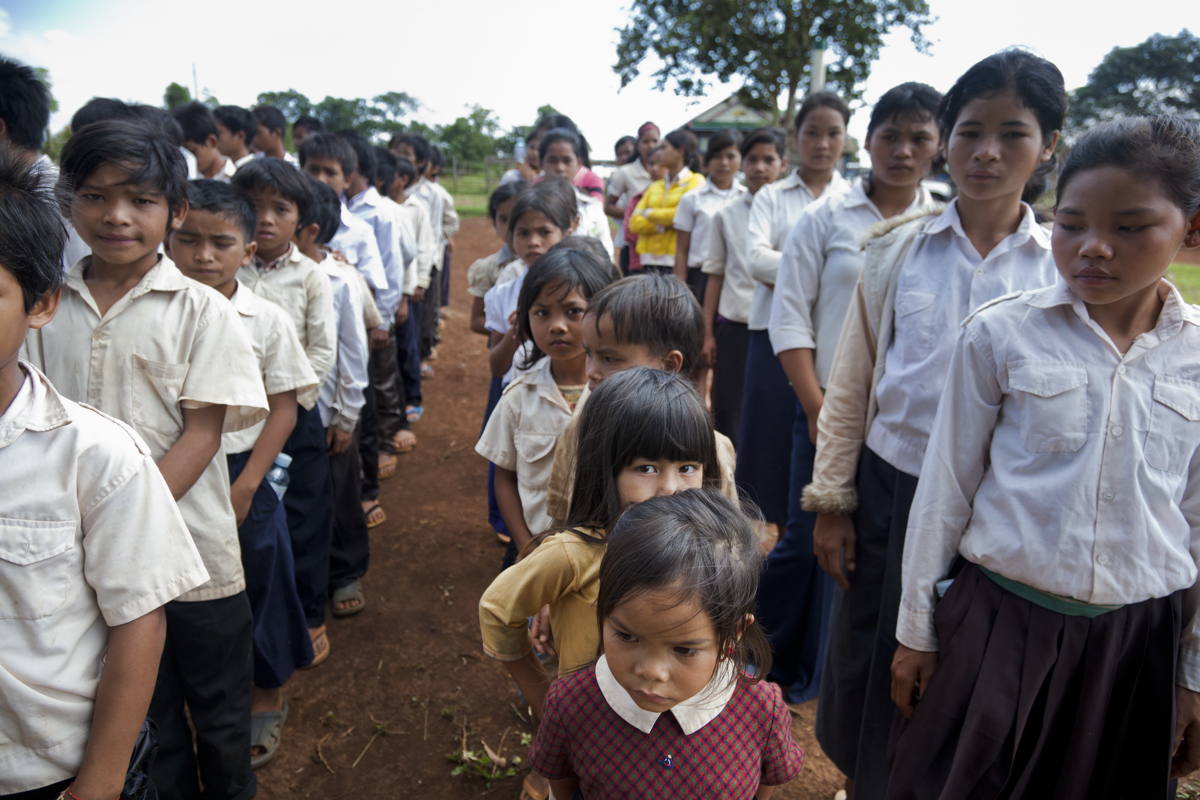 Children from a child friendly school in Pou Loung Village, Mondulkiri, gather to receive drinks and snacks during an enrolment ceremony