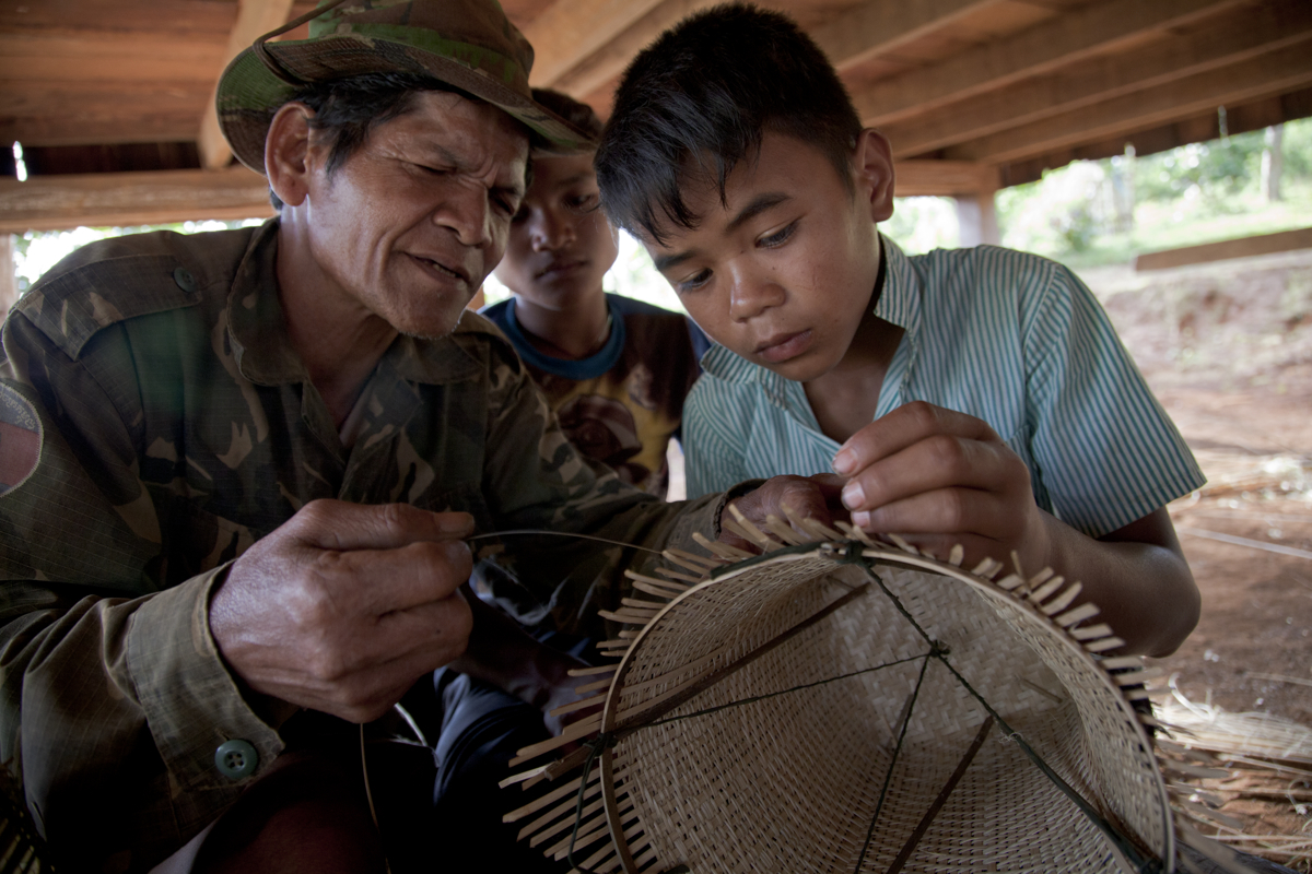 A man helps a young boy make a traditional basket in Dakdam Village. The baskets are then sold in town as souvenirs for tourists.
