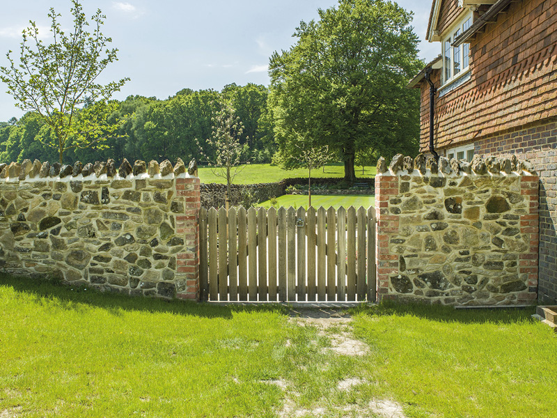 Stone walling and bespoke gates provide security and rustic charm to the side of this property