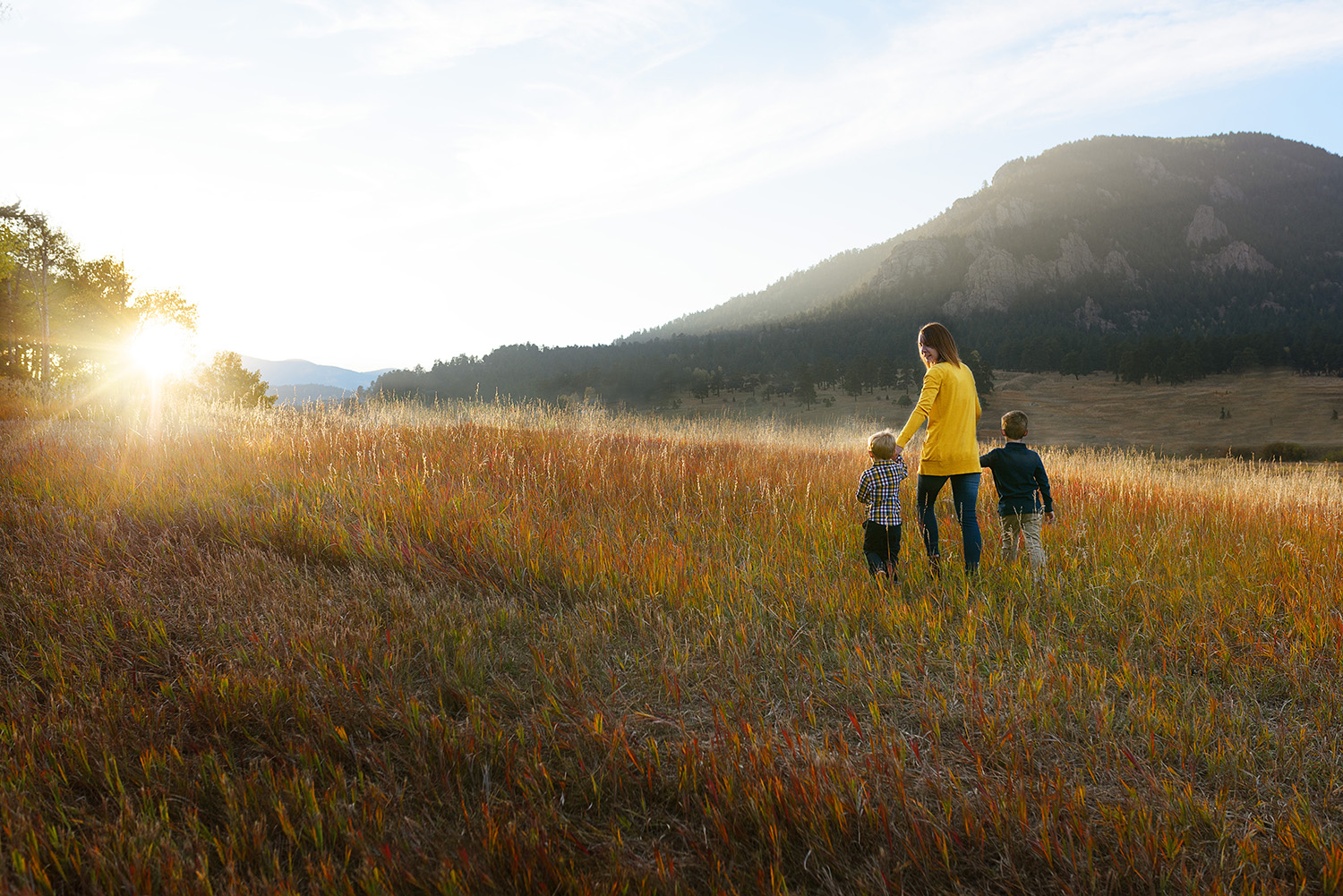 Mom With 2 Boys Walking toward Sunset in Fall Field.jpg